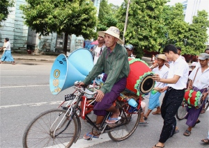 A trishaw driver association parading down Pansodan Street in Yangon, on their way to deliver offerings to a Buddhist monastery.