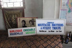 Signs on the stage at the Moustache Brothers' performance space in Mandalay. The  photograph shows Lu Maw with Aung San Suu Kyi.